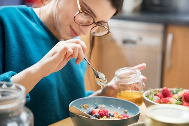 Woman Pouring Honey On Her Organic Breakfast